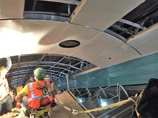 Installation of stainless steel reveal and custom curved ceiling panel in future passenger escalator wellway 4 (CM014B 11-15-2017)