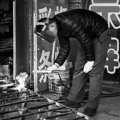 The street welder (Go-tea 郭天) Tags: qingdaoshi shandongsheng chine cn qingdao huangdao welder welding busy man work working job duty business alone lonely mask protection protected cold coat smoke sparks gloves tools iron metal stand standing worker young canon eos 100d 50mm prime street urban city outside outdoor people bw bnw black white blackwhite blackandwhite monochrome naturallight natural light asia asian china chinese shandong candid