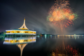 Dusk scene of Beautiful building with reflex on the lagoon and fireworks background in public park, Suanluang Rama 9, Thailand.