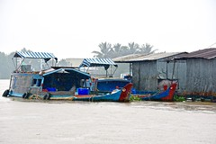 Downpour:  Boats, Dock, and Shed on the Mekong River (Ginger H Robinson) Tags: downpour heavy rain boat tire rope canopy bucket metal container dock plant shed mekong river water droplets bentre province delta southern vietnam southeast asia autumn
