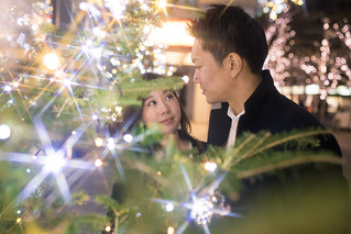 Happy couple looking at each other in Christmas lights