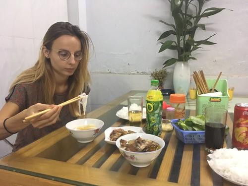 Julie mange un Bun Cha : des nouilles de riz et du porc grillé que l'on trempe dans une sauce sucrée salée.