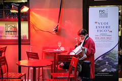 The woman in red (lorenzog.) Tags: bologna mercatodimezzo quadrilatero fico emiliaromagna italy red redlight people womandressedinred smoking reading newspaper nikon d700