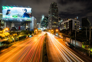 Night scene of light trail in road to Asoke district at the center of heart business district in Bangkok city downtown Thailand