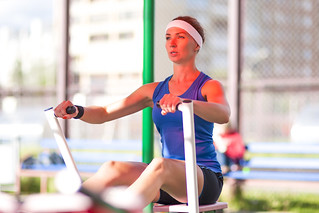 Sport Ideas and Concepts.Caucasian Female Athlete in Professional Outfit Having a Rowing Exercises for Legs and Arms Muscles.