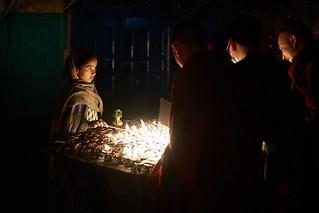Nepali girl lighting buddhist candles, Boudhanath, Kathmandu, Nepal