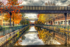 Autumn beauty in Lowell, MA. (macnetdaemon) Tags: hdr lowell highschool canal autumnleave autumn foilage river reflection sky cloud architecture building walkway skywalk railing canon 7d markii path park