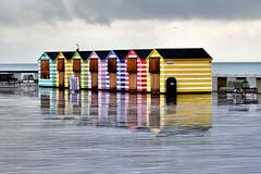 Pier Beach Huts (Geoff Henson) Tags: beachhuts huts photobooth pier sea seaside coast water reflection rain hastings sussex uk november nikon sigma horizontal colours outdoors clouds weather