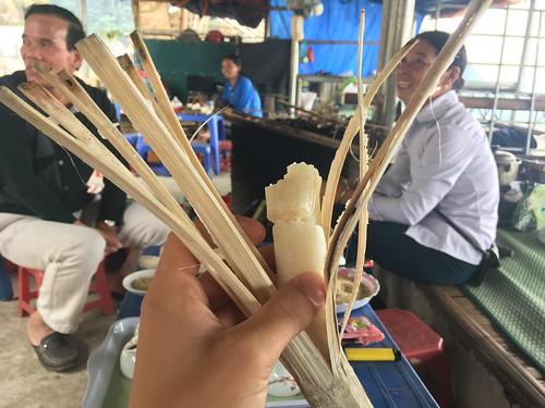 """Un """"bâton de riz"""". Du riz gluant cuit dans un bambou laissé auprès d'un feu. On le mange avec du sel."""