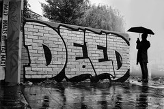 deeds not words (Daz Smith) Tags: dazsmith fujixt20 fuji xt20 andwhite city streetphotography people candid portrait citylife thecity urban streets uk monochrome blancoynegro blackandwhite mono graffiti art mural deeds umbrella woman rain silhouette