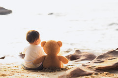 Baby and teddy bear sit togather on the beach (I love landscape) Tags: teddy bear beach travel doll sea bears brown couple two love sitting holding toy sand friendship childhood blue nature hug arms concept cute one background baby kid boy new born newborn small alone child romantic together valentines loneliness friends idea outdoors ocean gift summer sunrise sunset sun sit animal rock