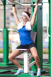Sport Concepts.Happy Flirting Caucasian Female Athlete in Having Her Rest Time During Training On Belly Workout Tool Outdoors.
