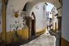 Evora, Portugal (Marian Pollock) Tags: europe evora street arch architecture people sunny shade cobblestones ruadafreiriadebaixo rustic