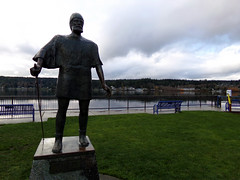 Viking statue by Liberty Bay, Washington (Nikki Cleveland) Tags: grass park sky water waterfront poulsbo washington wa wastate libertybay statue statues art sculptures sculpture viking vikingstatues norway flickr kodak waterfrontpark bench view cloud rain rainy rainyday peace peaceful bay
