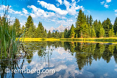 Water reflects cloudy skies and forest in front of the imposing Teton Mountain Range, Grand Tetons National Park, Teton County, Wyoming (Remsberg Photos) Tags: grandteton jackson landscape mountains nationalpark tetons west wyoming colorimage grandtetonnationalpark beautyinnature tetonrange mountainrange rockymountains mountain nature westernusa jacksonhole horizontal outdoors skyline sky traveldesintations tourism tranquilscene majestic impressive noble elevated splendid forest cloudy vast boundless broad expanse openspace snakeriver sunny spruce breathtaking usa