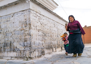 Tibetan nomad woman with her daughter holding a prayer wheel in her hand, Gansu province, Labrang, China
