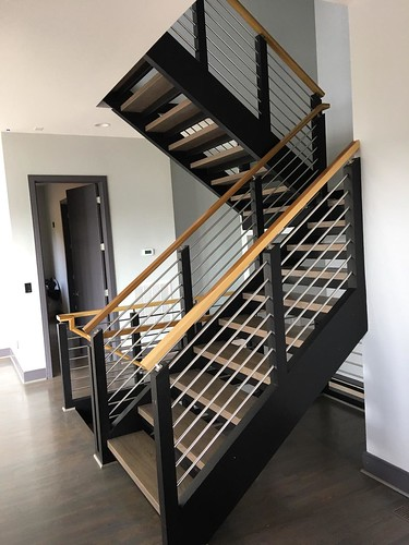 Midcentury modern staircase with horizontal metal balusters built and installed by Andronic's Construction co inc in Charlotte NC.