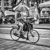Cyclist with umbrella Amsterdam. (James- Burke) Tags: amsterdam bikes blackandwhite bw cyclist holland monochrome netherlands panning rain street umbrellas