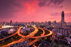 Roundabouts (Scintt) Tags: thailand bkk bangkok ratchaprarop tower mansion longexposure slowshutter travel tourism rooftop structure city cityscape skyline light trails expressway highway road street dramatic surreal glow sunset sun sky clouds evening dusk twilight orange magenta golden streaks baiyoke wideangle nikon1424mm modern billboards lines curves business hotels shopping malls office banks finance scintillation scintt jonchiangphotography night flyover futuristic epic traffic vehicles cars residential