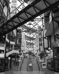 (Kelvin P. Coleman) Tags: canon powershot birmingham icc architecture building modern contemporary atrium steps stairs walkway gantry geometric lines poster banner advertisement sign signboard information text blackandwhite monochrome bw noiretblanc schwarzweiss blancoynegro indoor