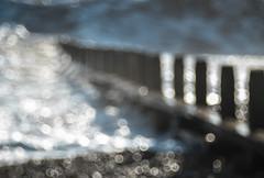 Wave (Fourteenfoottiger) Tags: swirly glistening bright glitter shimmer abstract waves sea surf groin beach seaside coast coastline defocused bokeh bubbles bubblebokeh meyergorlitztrioplan28100mm trioplan28100mm pebbles landscape ocean vintagelens vintagebokeh manual manualfocus seaspray backlit sunlight wintry blue blur water dancing light sparkly