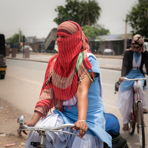 Young women cycling with their faces covered