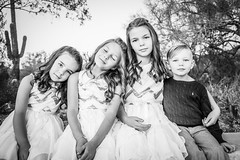 Three Sisters in White Dresses and Their Brother Sitting Looking Innocent - Black and White (Cole Eaton Photography) Tags: girl dress white little young beautiful kid child isolated portrait happy female pretty beach caucasian cute fashion childhood woman background beauty hair smiling lady fairy fun cheerful person summer joy happiness health people children small princess brother family sister sisters siblings related love black bw cactus desert b w eyes curls dresses hold rest innocent bright kids canon 5d mark iii