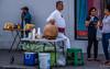 2017 - Mexico - Colima - Tuba Sales (Ted's photos - For Me & You) Tags: 2017 colima cropped mexico nikon nikond750 nikonfx tedmcgrath tedsphotos tedsphotosmexico vignetting tuba tubadrink colimacolima streetscene street cooler pigeon umbrella table costume stool