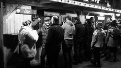festive market at night 07 (byronv2) Tags: edinburgh edinburghbynight night nuit nacht festivemarket christmasmarket market princesstreetgardens princesstreet mound newtown blackandwhite blackwhite bw monochrome peoplewatching candid street winter stall shop shopping food drink drinking
