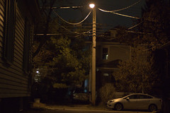 Men, you will be bigger. You don't have to fear the IRS any more. Call 8675309 (Dimi Sahn) Tags: night street car house nikone50mmf18 power lines pole cable