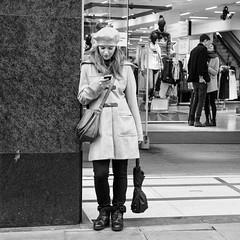 London 027 (Peter.Bartlett) Tags: square women window unitedkingdom city standing lunaphoto girl candid uk m43 couple bw wall noiretblanc shopfront olympusomdem5 people streetphotography doorway cellphone man urban woman bag niksilverefex urbanarte microfourthirds mobilephone shopwindow peterbartlett sign blackandwhite monochrome hat london england gb