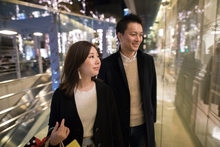 Young wife and husband walking together in night city