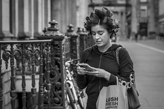 Lush (Leanne Boulton) Tags: urban street candid portrait streetphotography candidstreetphotography candidportrait streetportrait streetlife woman female girl face facial expression look emotion feeling mood mobile phone hair hairdo style stylish curls curlers fashion tone texture detail depthoffield bokeh naturallight outdoor light shade shadow city scene human life living humanity society culture lifestyle people canon canon5d 5dmarkiii 70mm ef2470mmf28liiusm black white blackwhite bw mono blackandwhite monochrome glasgow scotland uk