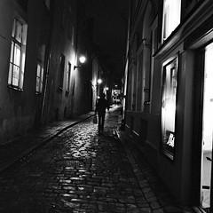 Tallinn (Peter Gutierrez) Tags: photo europe european eastern baltic estonia estonian estonians tallinn tänav kõnniteel avalik vanadest iidsetest keskaegsetest linnadest linnakeskustest kesklinnas öösel õhtul pimedas valgus vari must valge street sidewalk pavement public old ancient medieval city urban town center centre nighttime night time nocturne nocturnal nacht notte noche nuit evening dark light shadow black bw white square format peter gutierrez petergutierrez film photograph photography