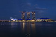 Marina Bay Sands evening time, Marina Bay, Singapore (tapanuth) Tags: marinabay sands hotel resort casino tower skyscraper art science museum evening dusk night cityscape city urban landmark travel tourism attraction modern futuristic light water waterfront longexposure bluehour twilight helixbridge shopping mall shop skypark rooftop sky colorful color asia southeastasia development finance business investment abstract central district downtown reflection river