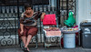 2017 - Mexico - Colima - Sidewalk Sales (Ted's photos - For Me & You) Tags: 2017 colima cropped mexico nikon nikond750 nikonfx tedmcgrath tedsphotos tedsphotosmexico vignetting streetscene street seated sitting female chairs foldingchairs selling fencing steps frown portrait cookies colimacolima woman