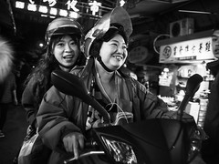 scooter grrls by dr.milker - Two scooterists riding through the South Airport Night Market in Taipei