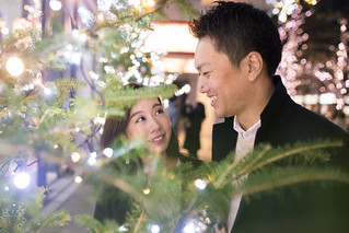 Young wife and husband looking at each other through Christmas tree