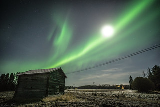 Auroras dancing on sky and Korkia's old barn in moonlight