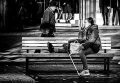 Get Well Soon. (Mister G.C.) Tags: blackandwhite bw image streetshot streetphotography photograph candid people woman lady female bench seat crutch injured unposed monochrome urban town city sonya6000 sonyalpha a6000 mirrorless telephoto zoom lens sel18105 18105mm sonyglens sony18105mmepz f4 mistergc schwarzweiss strassenfotografie hannover germany niedersachsen lowersaxony deutschland europe