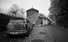 Park it there! (VanveenJF) Tags: mini germany kleve kleef sony car backlane home tower house man old vintage steeg auto parking job kempen deutschland holland nederland walking cloudy bw