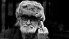 Noddy. (Neil. Moralee) Tags: bristolneilmoralee neilmoralee candid man face portrait hat fur noddy badge beard glasses finger rude gesture bristol market stnicholas old mature grumpy cross angry mad black white mono monochrome bw bandw blackandwhite grey gray shades neil moralee nikon d7200 people street santa father grandfather winter cold russian bigears toytown curmudgeon duffer