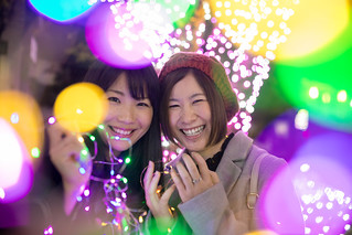 Happy young women covered with multi colored illumination in Christmas night