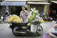 around the market (kuuan) Tags: chợphúnhuận caothắng voigtländerheliarf4515mm manualfocus mf voigtländer15mm aspherical f4515mm superwideheliar sonynex5n apsc hochiminhcity hcmc saigon vietnam street market flowers cycle