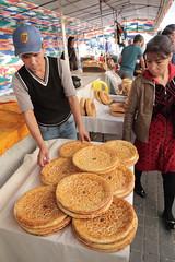 Fresh Bread (peterkelly) Tags: uzbekistan tashkent chorsubazaar digital asia canon 6d gadventures centralasiaadventurealmatytotashkent hat bread round table tent vendor seller