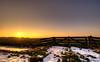 Putting the sun behind a fence. (Alex-de-Haas) Tags: 1635mm camperduin d750 dutch hdr holland hondsbosschezeewering nederland nederlands netherlands nikkor nikkor1635mm nikon nikond750 noordholland thenetherlands westfriesland belichting cloudless daglicht daylight fence handheld hek hemel highdynamicrange landscape landscapephotography landschap landschapsfotografie licht light lighting lucht onbewolkt skies sky sneeuw snow sundown sunset unclouded winter zonsondergang