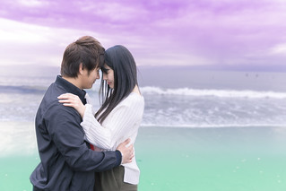High school student couple holding each other on beach