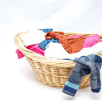 Laundry Basket with Clothes on a White Background thumbnail