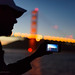 Man uses smartphone to photograph the Golden Gate Bridge at dusk
