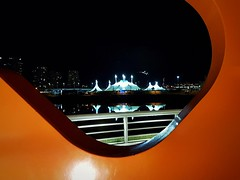 Circus tents through an orange frame (walneylad) Tags: vancouver britishcolumbia canada falsecreek scienceworld circus tents night evening december fall autumn dark lights railing water condos view urban city scenery orange publicart reflections cirquedusoleil bigtop kurios concordpacificplace